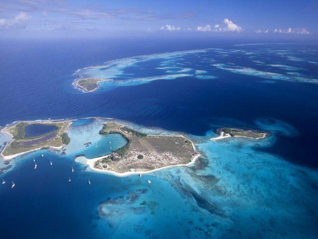 Cayo Madrizky en primer plano. luego se ve el canal tras la barrera coralina que se pierde hacia la derecha, el Sur